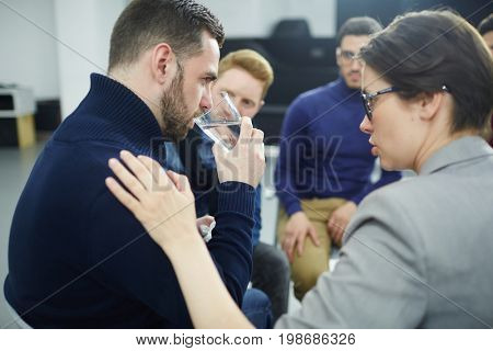 Helpful woman reassuring her co-worker with glass of water among other colleagues