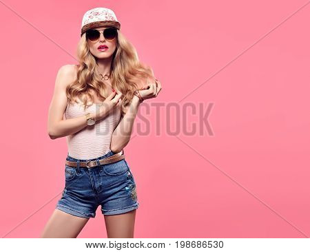 Fashion Model Sexy Girl. Hipster woman Cheeky emotion. Stylish Summer Outfit. Crazy Blond in Fashion Sunglasses, Glamour Denim Shorts.Trendy fashion Cap. Playful Summer Wavy Hairstyle