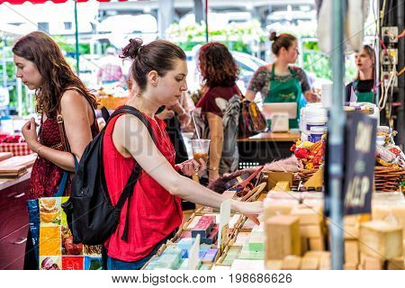 Montreal Canada - May 28 2017: Woman buying soap bars in Jean Talon market with people inside building in city in Quebec region
