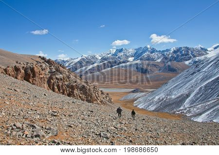 Two hunters walk down the mountain into the valley. The Tien Shan. The Issyk-Kul region Kyrgyzstan