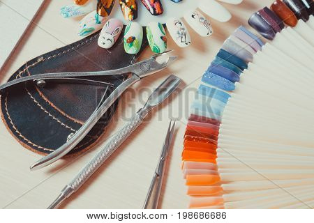 Table full of manicure utensils manicure tools nail polish colours on palette. Nails art accessories. Top view