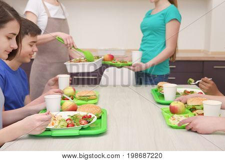 Children sitting at table in school cafeteria while eating lunch