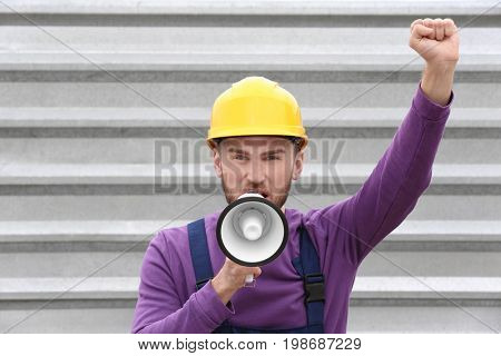 Protesting young man shouting into megaphone against metal fence