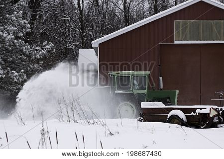 Hudson, Quebec - January 19, 2013 -- Wide view of a green tractor snow blower kicking up snow on a small farm with bare trees in the background near Hudson, Quebec on a bright overcast day in February