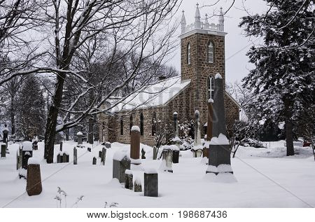 Hudson, Quebec - January 19, 2013 -- Wide view of a snow covered church with a small cemetery in the foreground in Hudson, Quebec on a bright overcast day in February.