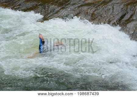 Rafting wipe out on white water rapid at Clear Creek White Water Park in Golden, Colorado