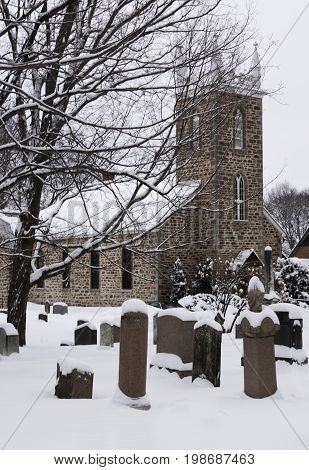 Hudson, Quebec - January 19, 2013 -- Vertical of a snow covered church with a small cemetery in the foreground in Hudson, Quebec on a bright overcast day in February.