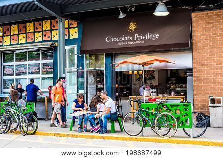 Montreal Canada - May 28 2017: People sitting outside chocolate shop outside Jean-Talon farmers market during bright sunny day