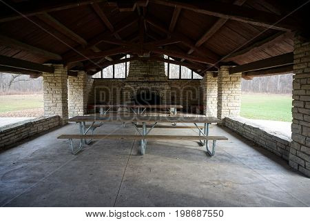 Picnickers may sit at picnic tables in the historic Shorewood Grove Shelter, in the Hammel Woods Forest Preserve in Shorewood, Illinois.