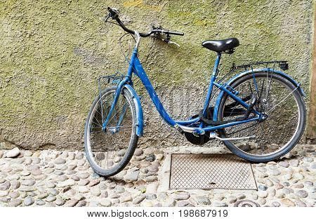 Old bicycle parked on a building wall in Ravenna Italy