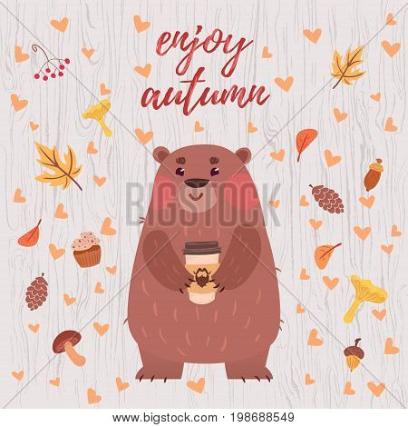 Cute enjoy autumn card with funny bear holding coffee mug and foliage on light wooden textured background.