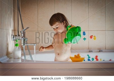 The child plays in the bathroom with a watering can