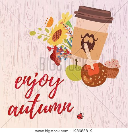 Colorful enjoy autumn greeting card with coffee cup sweeties and flowers on light textured wooden background.