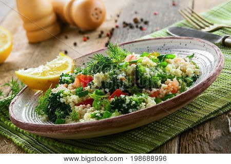 Plate with couscous and vegetables on a rustic wooden table. Traditional eastern healthy meal made of couscous broccoli tomato pepper onion and dill. Close-up shot.