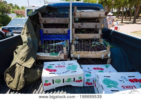 AVSALLAR TURKEY - JULY 01 2015: Boxes with fresh cherries for sale on the market (bazaar). The car body for delivery.