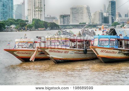 Bangkok Thailand - August 5th 2017: Hotels river Chao Praya and ferry station and ferry boat seen from bridge at station Saphan Taksin. On river are many small boats. Local ferry between two riversides is crossing river with many people on board.