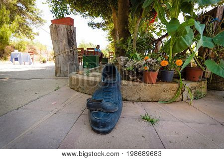 AVSALLAR TURKEY - JULY 01 2015: A giant and miniature rubber overshoes. Vignetting.