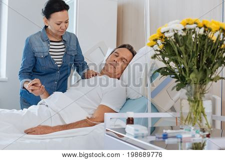 Pleasant surprise. Nice handsome ill man looking at the bouquet and holding his wifes hand while being at the hospital