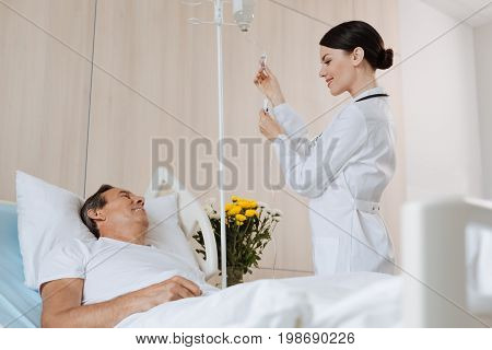 Interpersonal communication. Cheerful experienced nice therapist smiling and setting up the IV while interacting with her patient