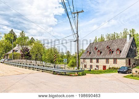 Deschambault Canada - May 29 2017: Stone cottage colorful house called Moulin de la Chevrotiere by road bridge and river on Chemin du Roy highway in Quebec