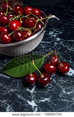 Several Red Sweet Cherries And Big Green Leaf On The Table. Fresh Organic Cherry In Colander On Dark