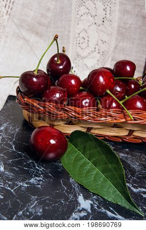 Several Red Sweet Cherries And Big Green Leaf On The Table. Fresh Organic Cherry In Yellow Wooden Ba
