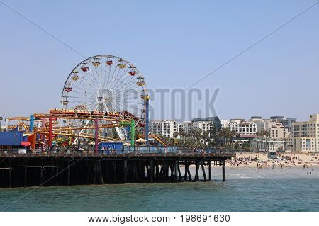 Santa Monica, California, USA - July 11, 2017: The Santa Monica Pier - the End of Route 66  - a 100 year old landmark with shops, restaurants and an amusement park called Pacific Park. It has been appeared in many movies and television shows.