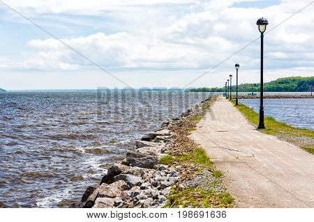 Portneuf Quebec Canada pier by harbor marina in Saint-Laurent or Saint Lawrence river with rocky path benches and nobody