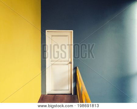 Vintage style with grain filter of empty hallway to small room of white door with yellow and green blue wall and wooden floor lighted with sun light from window on right side warm colour tone
