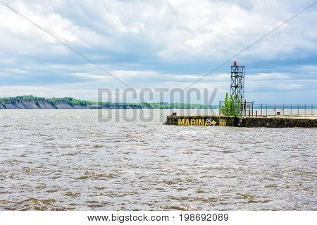 Pier In Saint-laurent Or Saint Lawrence River With Marina Sign And Lighthouse In Portneuf, Canada