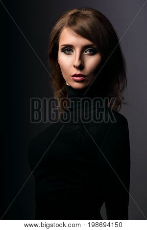 Beautiful Woman With Elegant Neck In Fashion Black Clothing Looking Mystic And Calm On Dark Shadow G