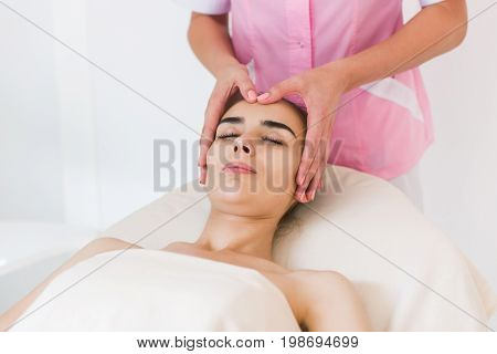 Facial massage beautiful girl. Portrait of a girl in a massage parlor. Beautician doing massage of female faces. Massage face girl close-up.