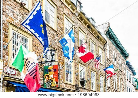 Quebec City Canada - May 29 2017: Old town street Rue Couillard with flags by Portofino restaurant