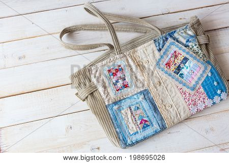 handmade, fashion, accessories concept -flatlay of charming women's bag made of velveteen and front part sewing in technique patchwork with colorful ornate snippets. it has two straps, lace and button