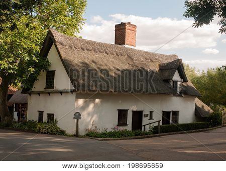 An Old White Barn Cottage With Thatched Roof In Summer Light