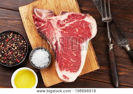 Raw T-bone steak cooking on wooden table. Top view