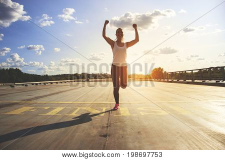 Winner As Style Of Life. Horizontal Shot Of Young Beautiful Woman In Sports Clothing Keeping Arms Ra