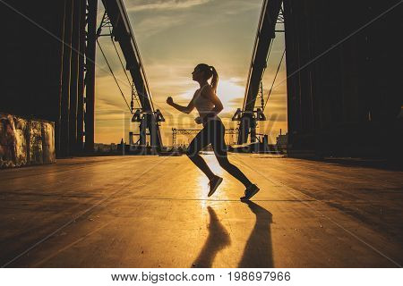 Evening Jog. Side View Of Young Attractive Woman In Sports Clothing Jogging On The Bridge With Indus