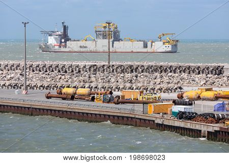 HARBOR CALAIS FRANCE - JUNE 07 2017: French harbor of Calais with dredging ship navigating outside of the harbor
