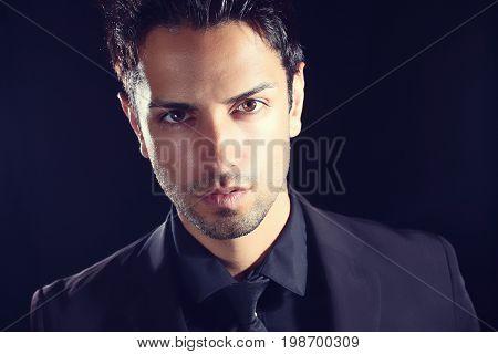 Portrait of handsome man in black suit on a black background