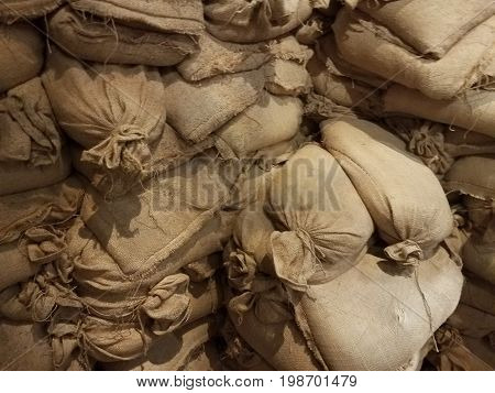 wall of brown canvas sandbags stacked up high