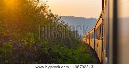 Traveling by train to sunset. Sunset scenery and a train gilded by sun, view from a train window. Thailand