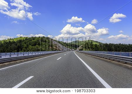 Highway outside the city receding into the highlands. Travel concept.