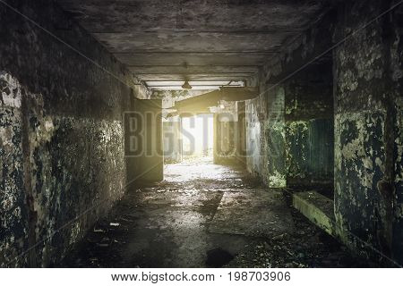 Dark hallway or corridor with peeling paint on the walls in an abandoned building and the light at the end of tunnel