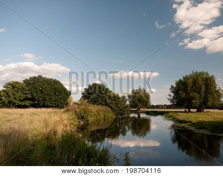 River Stour Running Through Dedham Countryside With Clear Sky And Lush Trees On A Summer's Day