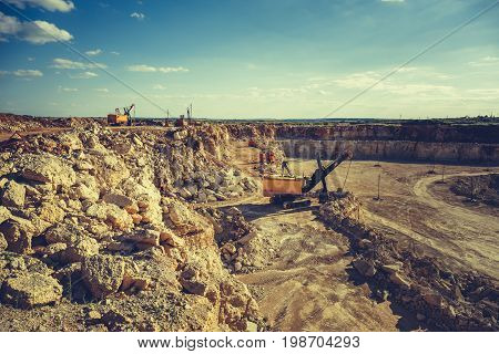Quarry equipment, excavator, heavy vehicles work in quarry, toned