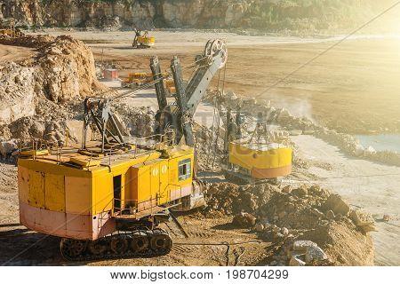 Quarry in sunlight. Big industrial vehicles, excavators, quarry equipment concept