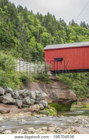 Old Red Covered Bridge Across A Low Flowing Stream, Large Rocky And High Treed Landscape