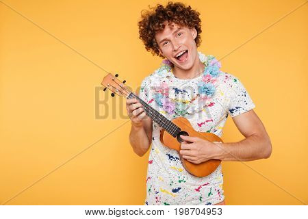 Attractive young man in summer clothes playing ukulele and singing isolated over yellow background