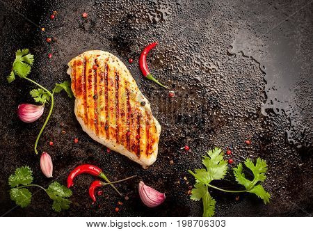 Spicy grilled chicken breast with chili and garlic on a roasting tin.